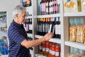 Senior Man Choosing Wine At Supermarket — Stock Photo