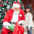 Santa Claus Giving Gift To Girl — Stock Photo #33100073