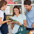 Saleswoman Assisting Couple In Buying Groceries — 图库照片