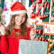 Woman In Santa Hat Carrying Shopping Bags — Stock Photo #33102589