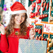 Woman In Santa Hat Carrying Shopping Bags — Stock Photo