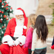 Santa Claus Looking At Children Standing In A Queue — Stock Photo #33104253