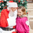 Santa Claus Whispering In Girl's Ear Against Christmas Tree — Stock Photo