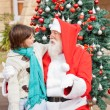 Boy Looking At Santa Claus In Front Of Christmas Tree — Stock Photo