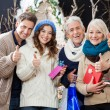 Happy Family Gesturing Thumbs Up In Christmas Store — Stock Photo #33108759