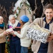 Happy Man Offering Christmas Present With Family In Background — Stock Photo #33109029