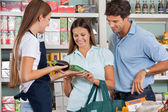 Prodavačka pomáhá páru v nákupu potravin — Stock fotografie