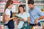 Verkäuferin bei, dass paar lebensmittel zu kaufen — Stockfoto