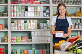 Saleswoman Displaying Pricetag In Grocery Store — Stock Photo