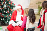 Santa Claus Looking At Children Standing In A Queue — Stock Photo