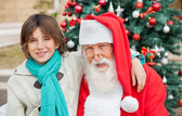 Boy With Arm Around Santa Claus Outdoors — Stock Photo