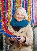 Senior Woman Holding Tinsels At Christmas Store — Stock Photo