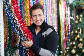 Young Man Choosing Tinsels At Store — Stock Photo
