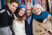 Happy Family Standing Against Tinsels At Store — Stock Photo