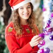 Owner Decorating Christmas Tree At Store — Stock Photo