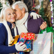 Man With Shopping Bags Kissing Woman At Store — Stock Photo