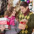 Happy Young Couple With Presents In Christmas Store — Stock Photo