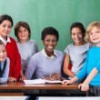 Teacher And Schoolchildren Smiling Together At Desk In Classroom — Stock Photo