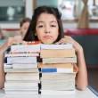 Sad Schoolgirl Resting Chin On Stacked Books At Desk — Foto de Stock