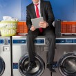 Businessman Using Digital Tablet In Laundry — Stock Photo