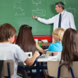 Stock Photo: Students Sitting At Desk While Teacher Teaching In Classroom