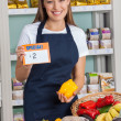 Saleswoman Holding Pricetag And Bellpepper In Supermarket — Stockfoto