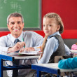 Girl And Teacher Sitting At Desk In Classroom — Stock Photo