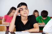 Thoughtful Teenage Schoolboy Sitting At Desk — 图库照片
