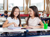 Happy Schoolgirl Sitting With Friend At Desk — Stock Photo