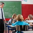 Teacher Looking At Students Sitting In Classroom — Stock Photo