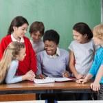 Female Teacher Teaching Schoolchildren At Desk — Stock Photo