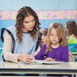 Teacher And Girl Reading Book With Children In Background — Foto de Stock