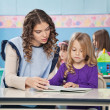 Stock Photo: Teacher And Girl Reading Book With Children In Background