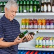 Senior Man Comparing Beer Bottles — Stock Photo
