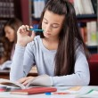 Schoolgirl Holding Pen While Reading Book In Library — Stock Photo #33206211