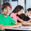 Boy Sitting At Desk With Friends Writing In Classroom — Stock Photo