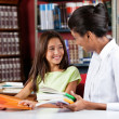 Happy Schoolgirl Looking Female Librarian In Library — Stock Photo