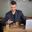 Businessman Messaging On Cellphone While Having Sandwich — Stock Photo #33207547