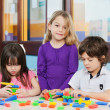 Stock Photo: Girl With Friends Playing Blocks In Kindergarten