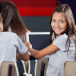 Schoolgirl Holding Digital Tablet At Desk In Classroom — Stock Photo #33208195