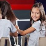 Schoolgirl Holding Digital Tablet At Desk In Classroom — Stock Photo