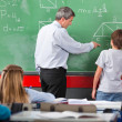 Teacher Assisting Schoolboy While Solving Mathematics — Stock Photo
