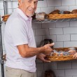 Senior Man Showing Muffins In Supermarket — Stock Photo