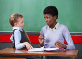 Female Teacher Scolding Schoolgirl At Desk — Stock Photo