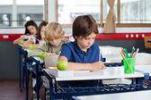 Crianças em idade escolar, escrita em livros na mesa — Foto Stock