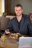 Businessman With Mobilephone And Laptop Having Meal In Restauran — Stock Photo