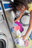 Woman Loading Dirty Clothes In Washing Machine — Photo