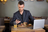 Businessman Messaging On Cellphone While Having Sandwich — Stock Photo