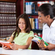 Librarian And Schoolgirl Looking Together At Book In Library — Stock Photo