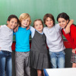 Happy Schoolchildren With Arms Around Standing Together In Class — Stock Photo #33252435